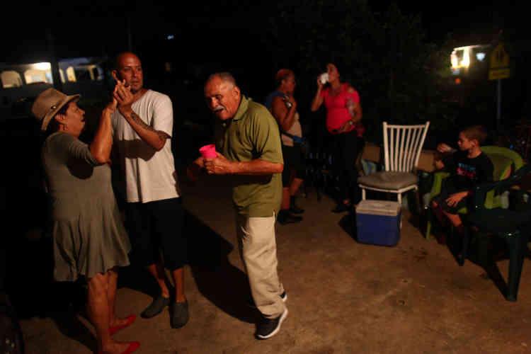 Des habitants d'El Sato, à Morovis, font la fête pour la nouvelle année, éclairés par les générateurs.