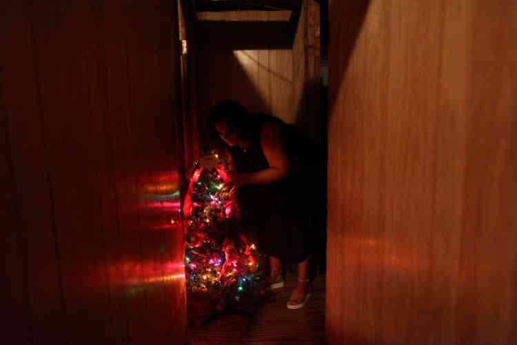 Une femme arrange le sapin de Noël décoré d'une guirlande électrique, le31décembre. Le gouverneur de l'île,Ricardo Rossello, avait promis le retour de l'électricitéà 95% au 15 décembre, tandis que le génie civil militaire américain a annoncé que le courant ne serait totalement rétabli dans l'île qu'en mai2018.