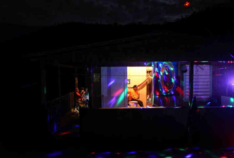 Des habitants du quartier d'El Salto, à Morovis, fêtent la nouvelle année. Des guirlandes de Noël alimentées par des groupes électrogènes décorent la maison, le31décembre.