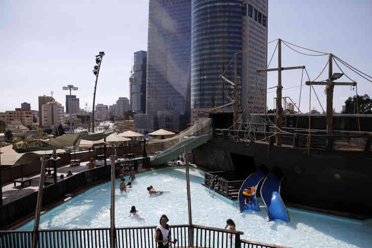 Des gens se baignent dans la piscine d'un parc de loisirs situé sur le toit du centre commercial Azrieli, dans le centre de Tel-Aviv.