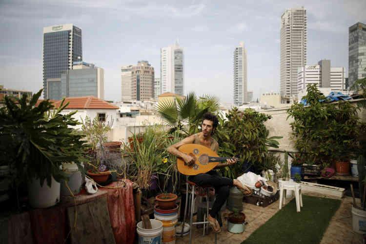Iyar Semel, 38 ans,musicien, joue du oud à l'endroit où ses deux autres colocataires et lui cultivent des herbes et des légumes.