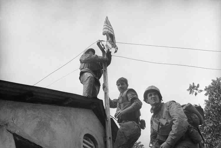 Des soldats américains attachent leur drapeau sur un poteau téléphonique près de la muraille de la citadelle de Hué.