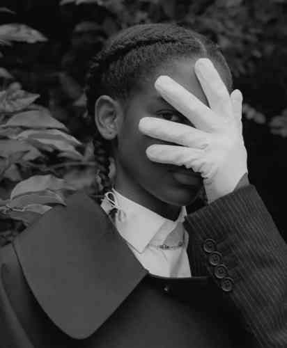 Cape en Mackintosh, Lanvin Homme. Veste de costume en laine à rayures tennis, Alexander McQueen. Chemise en coton, De Fursac. Collier en or, Au vase de Delft. Gants blancs en cuir d'agneau, Maison Fabre.