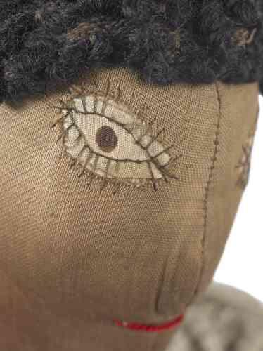 """«Le type de couture que l'auteure de cette poupée a mobilisé pour réaliser les yeux et les longs """"cils"""" de celle-ci se nomme""""un appliqué""""; on la retrouve dans leskilts(ou les courtepointes) africains-américains de l'époque. Elle évoque aussi les yeux de certaines marionnettes confectionnées par Paul Klee entre1916 et1925. Les poupées Neff représentent une immense diversité de personnes, allures, âges, et appartenances sociales, dont cette femme d'âge moyen, portant une robe de coton et un bandana, est exemplaire. »"""