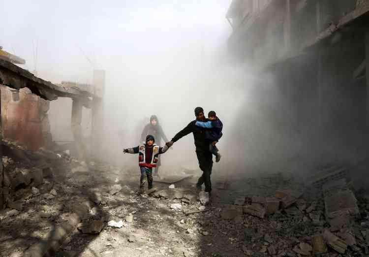 Des civils fuient après un raid, à Jisrine, le 8 février.