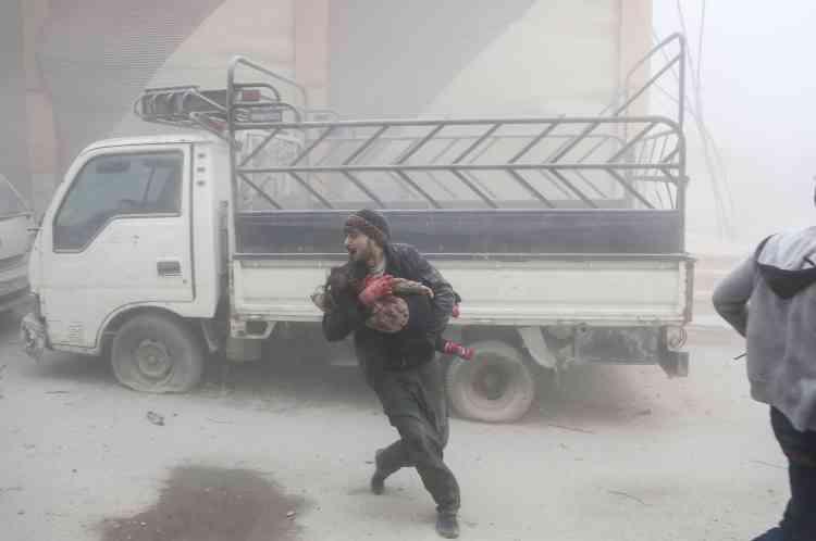 Un homme avec un enfant dans les bras, après un bombardement, le 6 février.