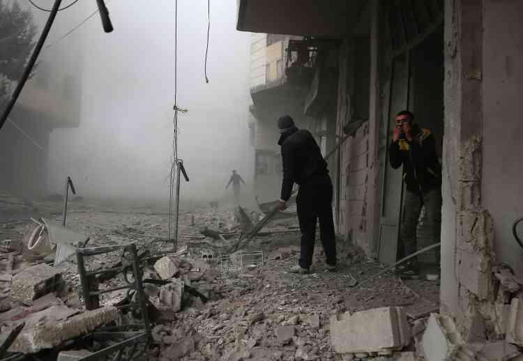 Des membres de la défense civile syrienne cherchent des victimes blessées dans les décombres, à Hamouria, le 20février.