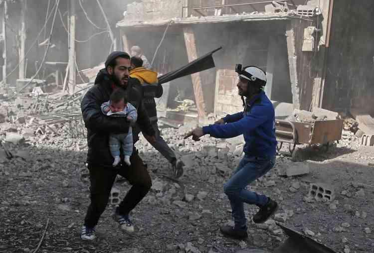 Un homme porte un bébé blessé, à Hamouria, le 19février. Près de 60enfants ont été tués depuis dimanche par les violents bombardements du régime sur le fief rebelle de la Ghouta.