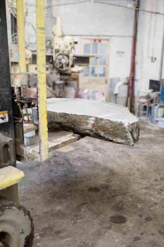 Dans la fabrique, une nouvelle tranche de granit s'apprête à être divisée en plusieurs cylindres.