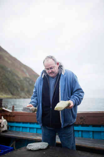 Mark, un pêcheur de Girvan, sur la côte, montre les deux principaux types de granits utilisés pour la production de pierres de curling : le bleu et le vert.