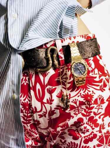 Montre Royal Oak quartz en or jaune, glace saphir et sertie de diamants, Audemars Piguet. Bracelet GG Running en or jaune, topazes bleu, orange, jaune et saphirs ; ceinture en cuir imprimé, Gucci. Chemise en coton imprimé, Charvet. Pantalon en coton imprimé, Holiday.