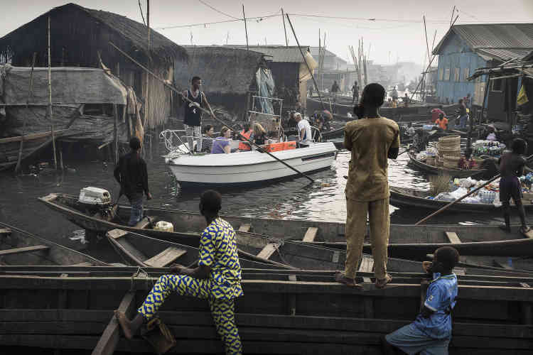 Un bateau de touristes conduit à travers les canaux de la communauté Makoko, un ancien village de pêcheurs développé en une énorme colonie informelle, sur les rives du lagon de Lagos au Nigéria, le 24 février 2017.