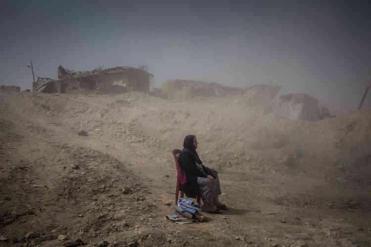 Après la reprise de l'ouest de Mossoul, en Irak, Nadhira Aziz, assise à quelques mètres de sa maison détruite dans un bombardement, attend qu'on extraie les restes des corps de sa soeur et de sa niècedes décombres.
