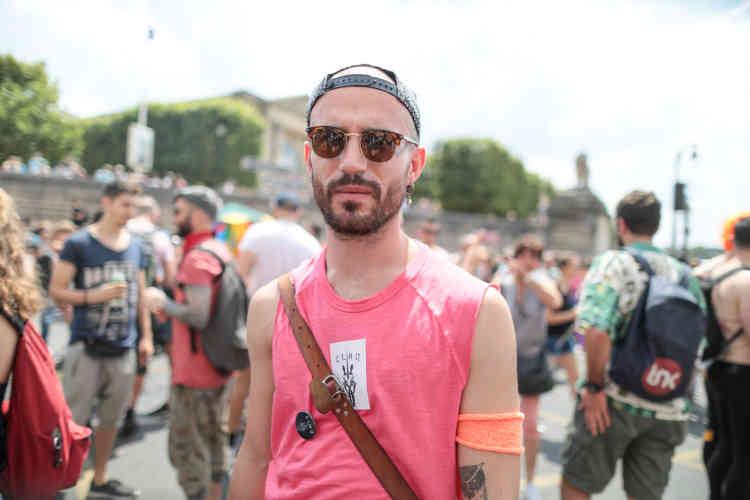 Camille L., membre du CLAQ dénonce la tentative de récupération du mouvement LGBT par la majorité, avec l'Assemblée nationale pavoisée aux couleurs arc-en-ciel.