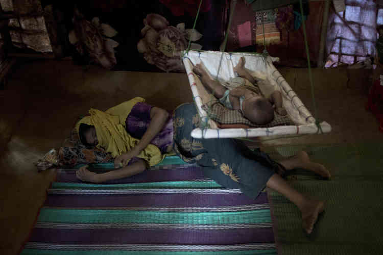 « M » se repose sur le sol de son abri, avec son petit garçon au-dessus d'elle.