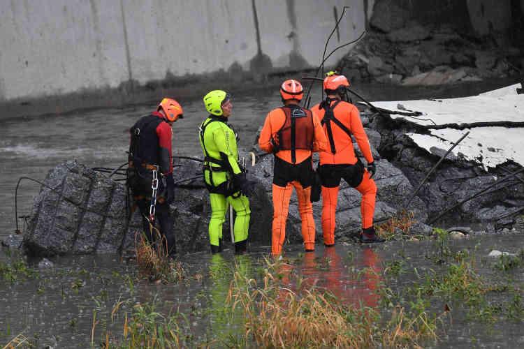 Des secouristes travaillent parmi les décombres du pont autoroutier.