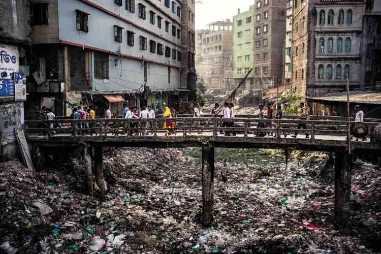 Le canal qui se jette dans la rivière Buriganga, à Dacca, au Bangladesh, n'est plus qu'un amoncellement de déchets qui empêchent l'eau de couler. Cette rivière, qui se meurt, compte parmi les plus polluées au monde. Les ateliers de confection installés sur les rives déversent chaque jour de grandes quantités de produits chimiques et de détritus. En suivant les cinq cours d'eau qui encerclent la capitale bangladaise, le photographe Gaël Turine a documenté les conséquences de l'industrialisation massive dans cette ville. Un désastre écologique qui s'explique par l'explosion démographique, la corruption et la misère.