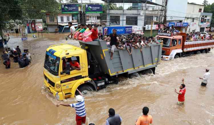 Des indiens quittent une zone à risque alors que les eaux ont ravagé la route nationale 47 dans le district d'Ernakulam de Kochi. Vendredi, le bureau de M. Vijayan a de nouveau mis en garde les 33 millions d'habitants de l'Etat sur Twitter : «Tous les districts à l'exception de celui de Kasargod sont en alerte rouge. Les pluies torrentielles pourraient affecter ces 13 districts. Tout le monde doit faire très attention. »