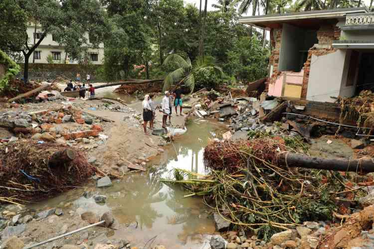 Des habitants deKannappankundu constatent les dégâts d'une inondation soudaine, le 10 août.