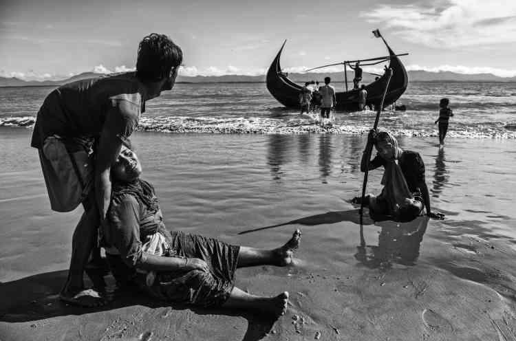 Des réfugiés, épuisés après leur voyage, sur une plage au bord du fleuve Naf, qui marque la frontière entre la Birmanie et le Bangladesh. La traversée de ce fleuve est l'une des voies utilisées par les musulmans rohingya, qui fuient les persécutions dans leurs villages de Birmanie. Le photographe Kevin Frayer a séjourné deux fois au Bangladesh pour documenter cet exode forcé. Dans sa série de clichés, il a voulu mettre l'accent sur des histoires personnelles et sur la fatigue qu'engendrent d'aussi longs déplacements, qui ne sont pas la fin des ennuis pour les réfugiés. A l'arrivée dans les camps, la malnutrition, le choléra et d'autres maladies souvent mortelles les attendent.