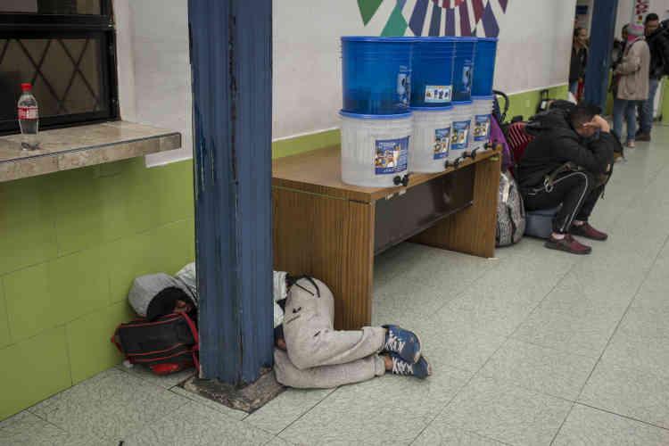 Un voyageur dort sur le sol près des services de migration équatoriens.