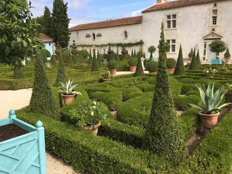 Parterres de buis, topiaires, succulentes en pots, lauriers et agrumes en caisses colorées déclinent une grammaire des jardins où les styles se mélangent avec élégance.