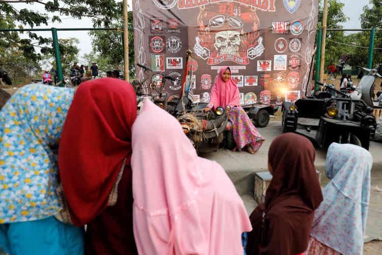 De jeunes femmes se prennent en photo parmi des Vespa modifiés au festival de Semarang, dans le centre de l'île de Java, le 21 juillet.
