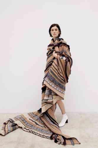 Cape poncho, patchwork de tissus, Stella McCartney. Bottines en cuir lisse, Céline.