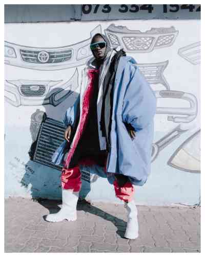 Manteau Superposition en nylon et pull en laine, Balenciaga. Lunettes de soleil, Mykita. Bottes en cuir et nylon, Prada.
