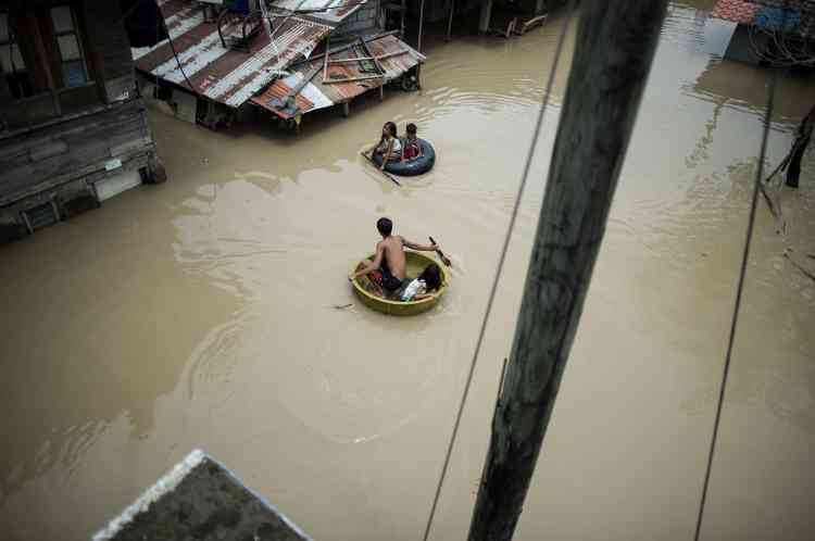 Des enfants utilisent bassine et bouée pour traverser une rue inondée à Calumpit, aux Philippines, le 16 septembre.Après avoir ravagé le nord de l'archipel, la tempête a traversé la mer de Chine méridionale, son centre passant à une centaine de kilomètres au sud de Hongkong, et plus près encore de Macao.