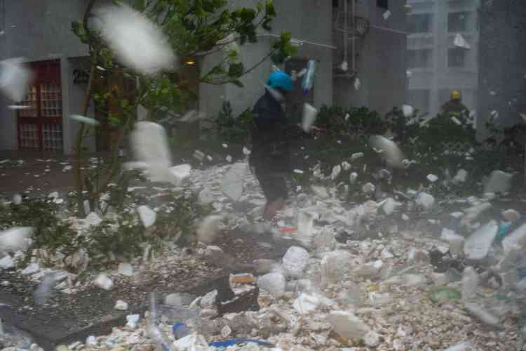 Un photojournaliste parmi les débris plastiques soufflés par la tempête à Hongkong, le 16 septembre. Lesautorités chinoises ont indiqué avoir évacué plus de 3millions de personnes dans le sud du pays.