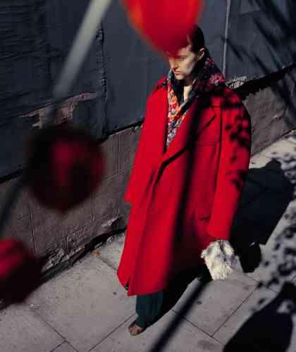 Manteau en laine sur manteau à capuche imprimé fleurs, pantalon enlaine et bottines encuir, Vetements. Pochette callie en satin à franges, Jimmy Choo.