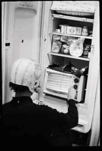 Casque de footballaméricain vissé sur la tête, Basquiat se met en scène avec un téléviseur dans son réfrigérateur.