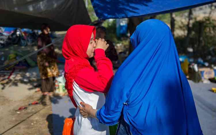 Sitti Damra (à gauche) et sa sœur Samsinar Zaid Moga lors de leurs retrouvailles dans un centre d'évacuation de fortune à Palu, le 1eroctobre.
