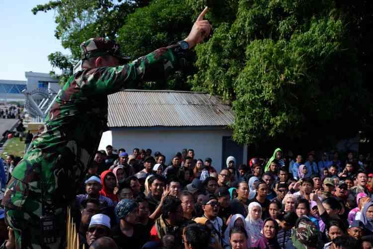 Des habitants essayent de pénétrer dans l'aéroport de Palu, dans l'espoir d'être évacués, le 30septembre.Le président Joko Widodo a déclaré aux journalistes, à Djakarta, que l'évacuation des personnes est sa priorité.