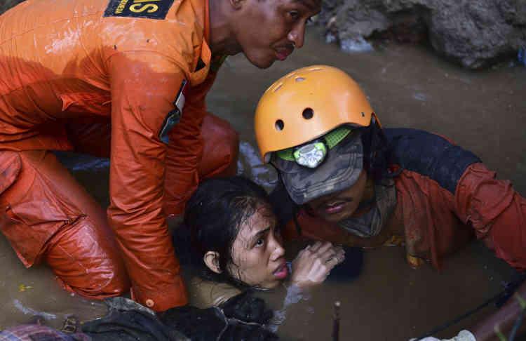 Des sauveteurs porte secours à une victime du tremblement de terre âgée de 15ans, à Palu, le30septembre.La plupart des victimes a été recensée dans cette agglomération de 350 000 habitants, située sur la côte ouest des Célèbes.