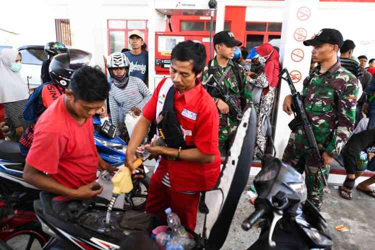 Des soldats surveillent une station-service, le 1eroctobre, alors que des survivants viennent chercher de l'essence pour fuir la ville de Palu.Un responsable militaire a dit espérer que 1500personnes puissent être évacuées chaque jour; les enfants, les femmes et les blessés étant prioritaires.