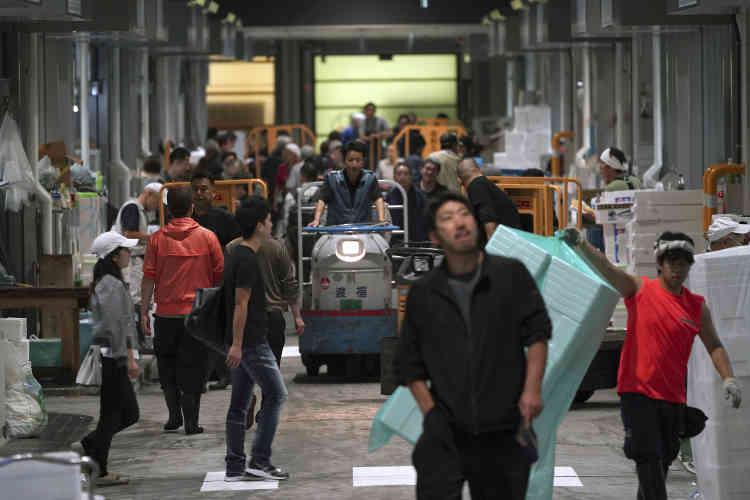 Des employés transportent des marchandises lors de la journée officielle d'ouverture du marché de Toyosu, jeudi 11 octobre.600 milliards de yens, ou 4,6 milliards d'euros : c'est le coût estimé du déménagement, une opération colossale qui s'est déroulée sur près de cinq jours et a vu 900 entreprises quitter les lieux.