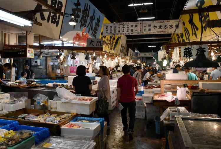 Des magasins de courtiers en poissons au marché de Tsukiji, à Tokyo, le 3 septembre. Après une fabuleuse histoire de 83 ans, le plus grand marché aux poissons du monde, qui constitue également un formidable attrait touristique pour ses enchères de thon d'avant l'aube, va déménager. Le site sera fermé pendant cinq ans et pourrait être transformé en parc à thème gastronomique.