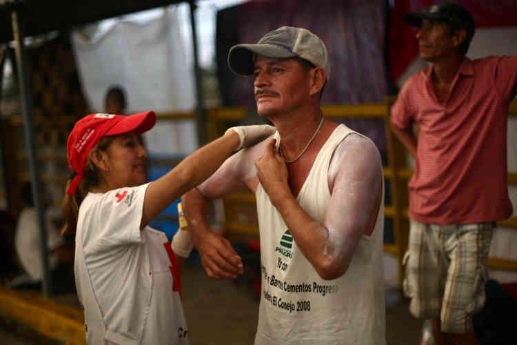Sur le pont d'Hidalgo, entre le Guatemala et le Mexique, une membre de la Croix-Rouge aide un homme à se mettre de la crème solaire, le 21 octobre.