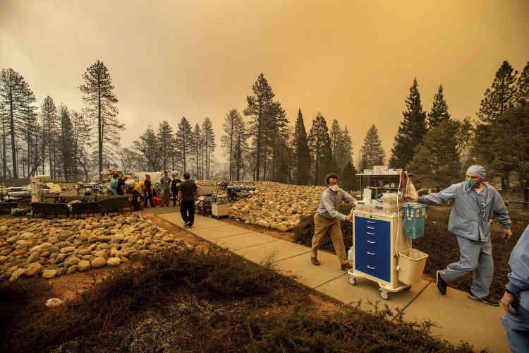 Des équipes médicales déplacent du matériel alors que l'hôpital de Feather River, situé à Paradise, a été partiellement brûlé.