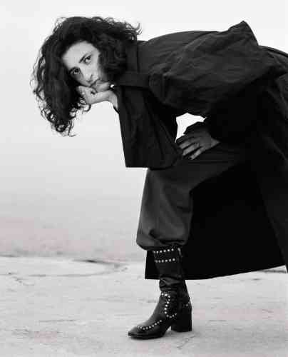 Manteau en coton enduit, Yohji Yamamoto. Pantalon en drap de laine, Dries Van Noten. Botte en cuir clouté, Coach.