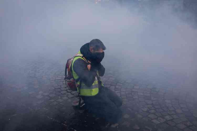 Un« gilet jaune» essayant de se protéger des gaz lacrymogènes lors de l'évacuation des Champs-Elysées, le 15 décembre.