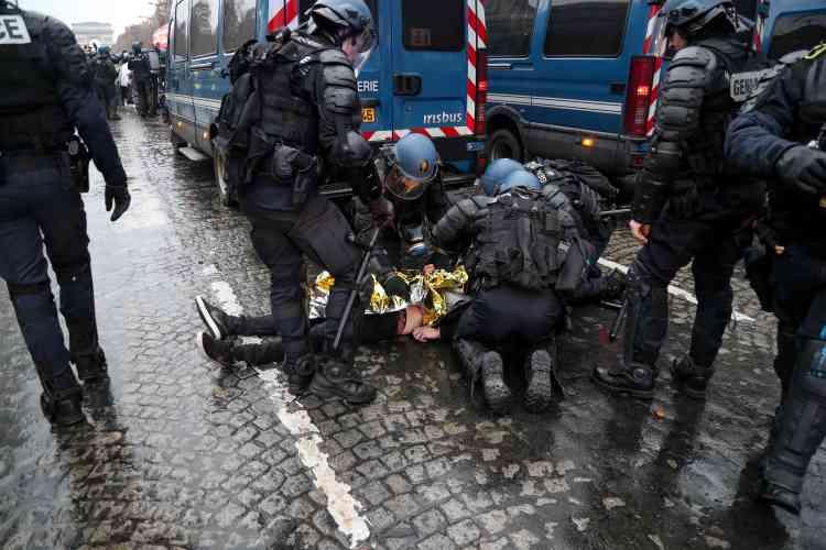 Des policiers portent les premiers secours à un « gilet jaune» blessé sur l'avenue des Champs-Elysées à Paris, le 15 décembre.