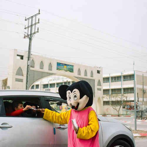 Un employé déguisé en Mickey distribue des prospectus pour un parc d'attractions aquatiques récemment ouvert.