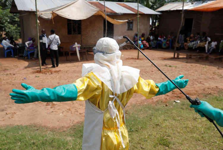 Un travailleur sanitaire se fait décontaminer après avoir porté un bébé qui a probablement succombé au virus Ebola à Beni, dans la province du Nord-Kivu, en République démocratique du Congo le 18 décembre.