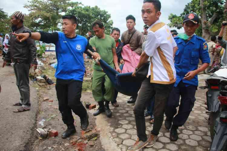 Aidés par des volontaires, les secours évacuent un cadavre àSouthLampung, au sud de Sumatra le 23 décembre. Le tsunami a fait au moins 281 morts.