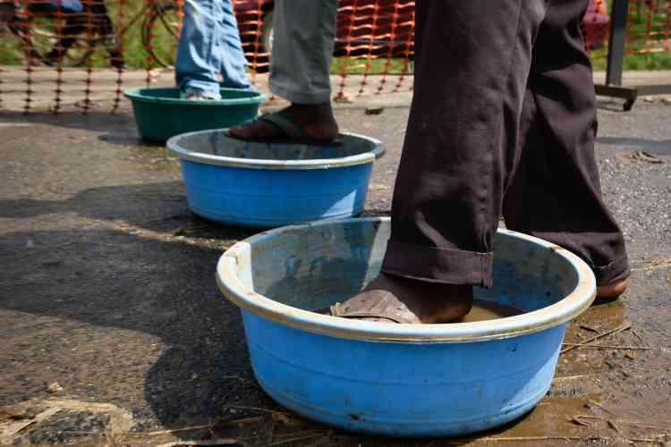 Des gens venant de RDC se lavent les pieds à un point de contrôle sanitaire à la frontière entre l'Ouganda et la RDC à Mpondwe, dans l'ouest de l'Ouganda, le 12 décembre.