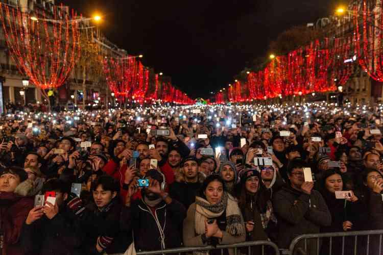 La foule, 250 000 personnes selon la préfecture de police, attend minuit sur les Champs-Elysées.
