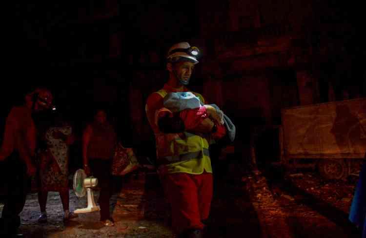 Un pompier évacue un bébé dans le quartier de Luyano, dans la nuit de dimanche à lundi.